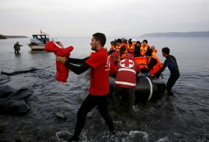A Red Cross volunteer carries a refugee baby at a beach on the Greek island of Lesbos
